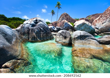 The Baths beach area major tourist attraction at Virgin Gorda, British Virgin Islands with turquoise water and huge granite boulders - stock photo