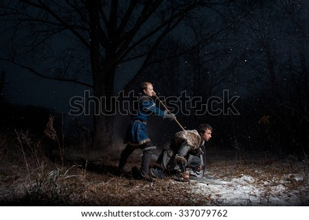 The battle between medieval knights in the style of Game of Thrones in winter forest landscapes. A warrior with a spear kills swordtail - stock photo
