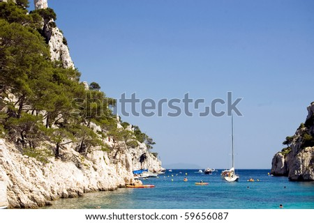 The bay Calanques d'En-Vau with swimmers and sailboats in the summer - stock photo