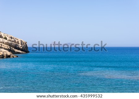 The bay of Matala in south-central Crete. In the Libyan Sea, the island Paximadia. In the foreground, the cliff of the bay. Matala is known as a hippie destination from the seventies - stock photo