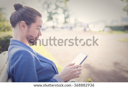 The bearded hipster photographer in blue jacket running on the tablet in a park in St. Petersburg. - stock photo