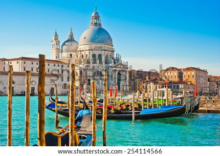 The beautiful and famous tourist destination spot Basilica Santa Maria della Salute in sunny weather on the azure blue Grand Canal, the best place in Venice, Italy postcard image - stock photo