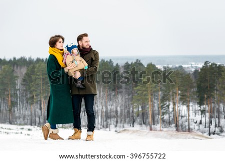 The beautiful and happy family walks in the winter outdoors