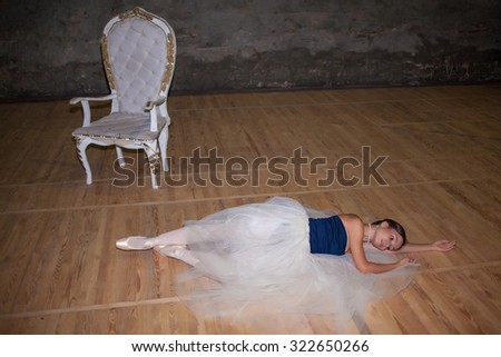The beautiful ballerina lying in long white skirt on wooden floor background