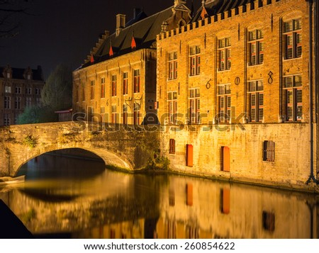 The beautiful Belgian city of Bruges by night reflected in the water - stock photo