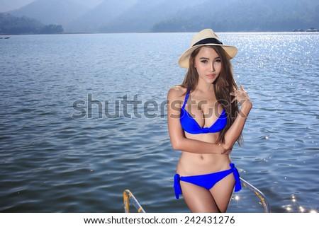 The beautiful bikini model posing on the Lake - stock photo