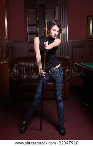 The beautiful blonde aims in the course of game at billiards - stock photo