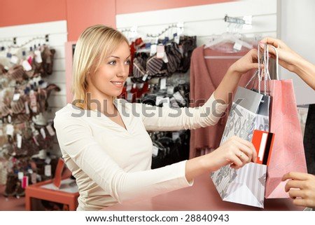 The beautiful blonde transfers a credit card to the seller in underwear shop - stock photo