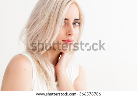 The beautiful blonde with big blue eyes looking into the camera. The concept of hair care, purity. studio photo on white background - stock photo