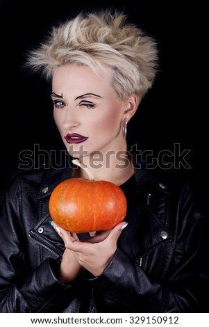 the beautiful blonde with creative make-up in a black leather jacket stares askance and holds in hands small pumpkin on a black background - stock photo