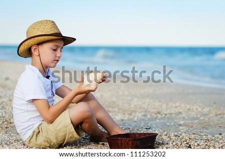 The beautiful boy playing a sea shell on a beach - stock photo