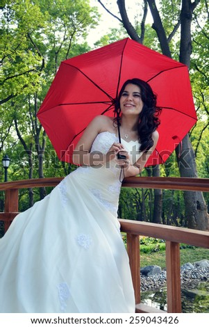 The beautiful bride with a parasol on nature - stock photo