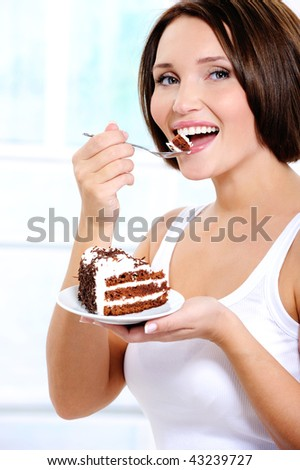 The beautiful cheerful young woman eats a sweet cake - stock photo