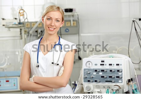 The beautiful doctor costs near to the volume ventilator - stock photo