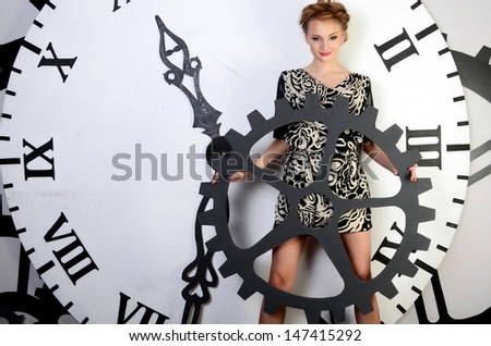 The beautiful elegant  woman on clockwork background - stock photo