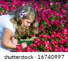 The beautiful girl among flowers - stock photo