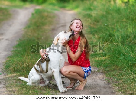 The beautiful girl and dog have sat down on a forest footpath. Dog of breed Labrador. - stock photo