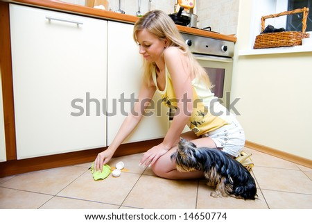 The beautiful girl cleans the broken egg