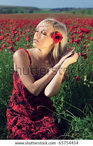 The beautiful girl dreams in the field of red flowers - stock photo
