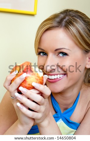 The beautiful girl eats an apple
