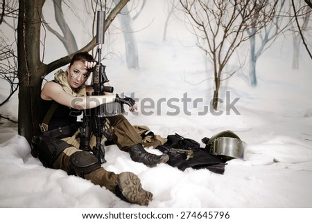 The beautiful girl in a military uniform with the weapon sits - stock photo