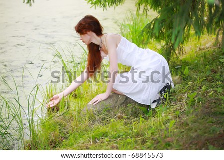 The beautiful girl in a white sundress on the bank of wood lake