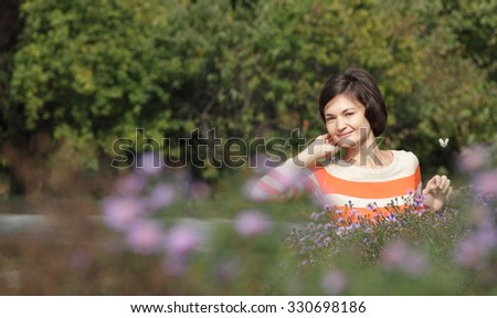 The beautiful girl in park against blossoming colours and decorative bushes