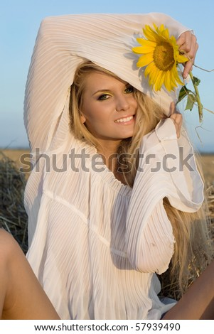 The beautiful girl in the field with a sunflower in a hand
