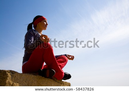 The beautiful girl is engaged in yoga on the rock against the blue - stock photo