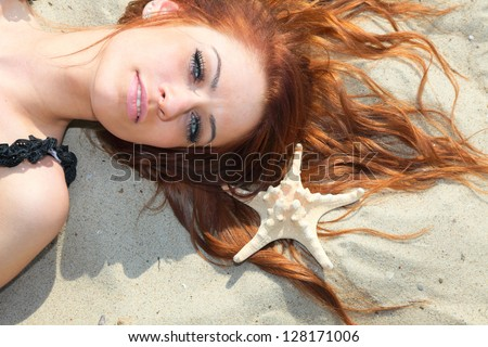 The beautiful girl lies on sea coast with shells nature vacation woman - stock photo