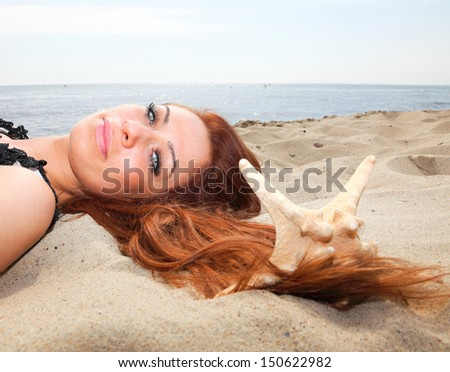 The beautiful girl lies on sea coast with shells nature vacation woman