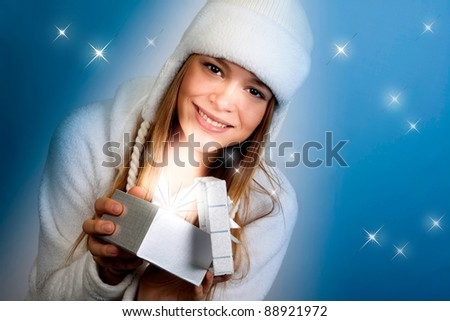 The beautiful girl looks a gift. Christmas. - stock photo
