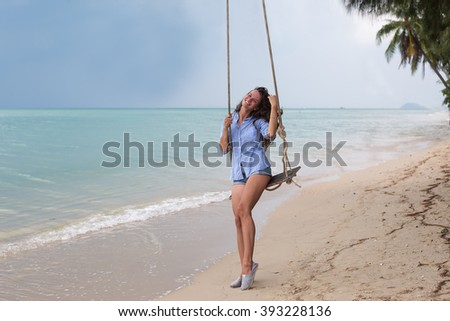 The beautiful girl on a swing, on the tropical beach, with a smile upon the face