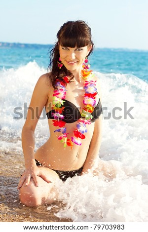 The beautiful girl on sea coast with flowers