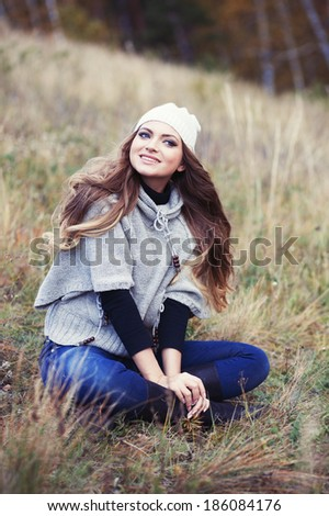 The beautiful girl sitting on a grass - stock photo
