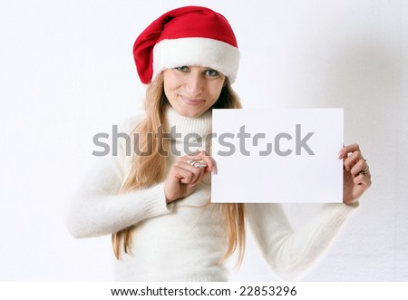 The beautiful girl smiles in a New Year's cap and holds white sheet - stock photo
