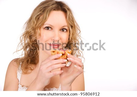 The beautiful girl the teenager eats sweet a pie on a white background