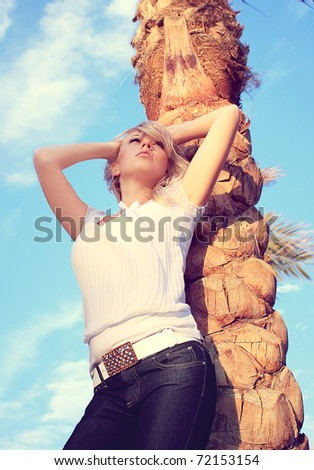 The beautiful girl under a palm tree on a beach - stock photo