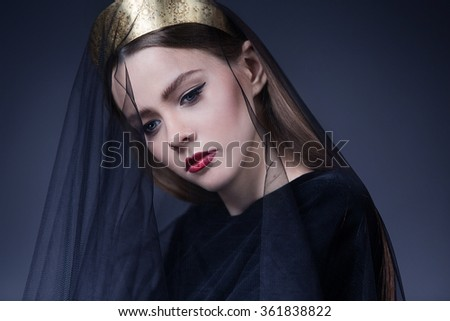 the beautiful girl with a black veil on a face, red lips and a gold crown - stock photo