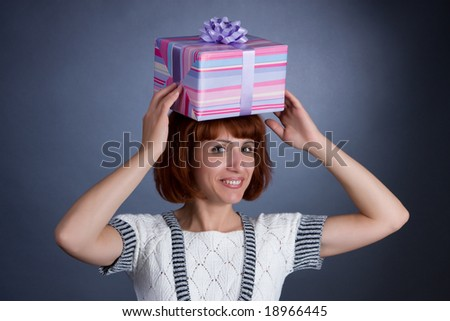 The beautiful Girl with a box of gifts on a head - stock photo