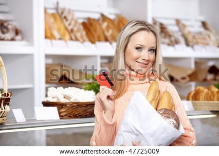 The beautiful girl with a credit card in shop