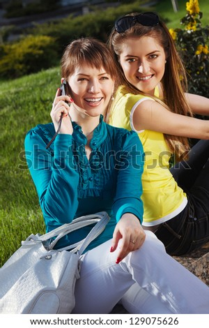The beautiful girl with girlfriend and talking with cellphone