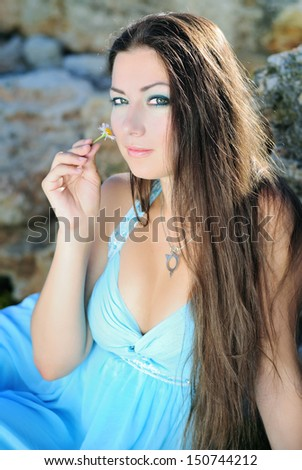 The beautiful girl with long hair on stones