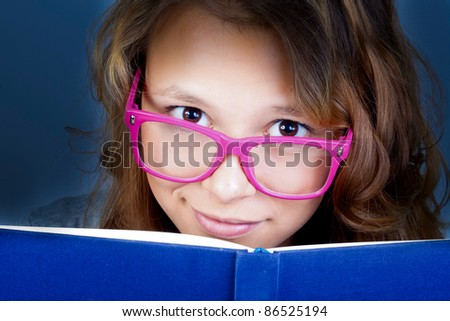 The beautiful girl with the dark blue book. Training. Points. The pink. Reading. - stock photo