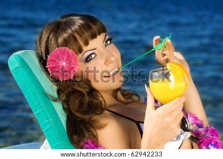 The beautiful girl with the Hawaiian flowers on a neck - stock photo