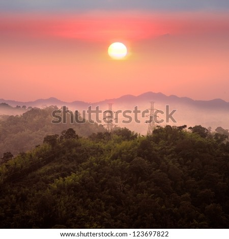 the beautiful landscape sun ,power poles and mountain in nature - stock photo