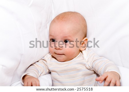 The beautiful little boy sitting in a bed
