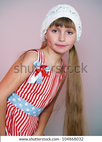 The beautiful little girl in a summer dress and a knitted white beret - stock photo