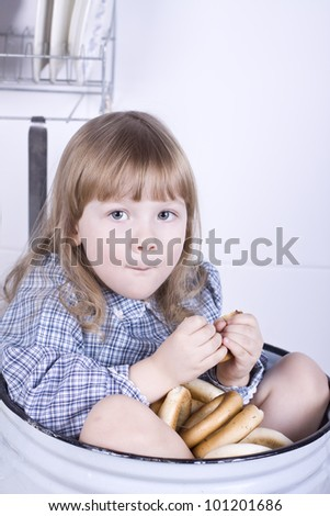 the beautiful little girl sits in a big pan and eats a bagel
