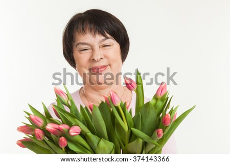 the beautiful mature woman admires to a bouquet of tulips - stock photo